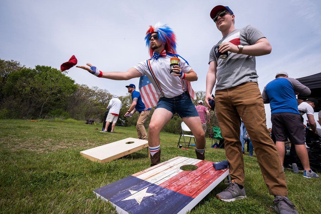 Fans Clayton Ferrell (center) and Ryan Handy play cornhole as they tailgate before the Texas Rangers Opening Day game against the Chicago Cubs at Globe Life Park on Thursday, March 28, 2019, in Arlington. (Smiley N. Pool/The Dallas Morning News)