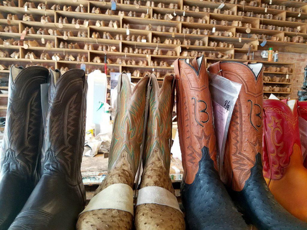 Boots in progress stand in front of a wall full of different sizes of boot foot forms at M.L. Leddy's custom boot shop in San Angelo.