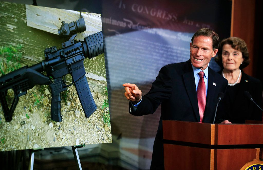 Sen. Richard Blumenthal, D-Conn., with Sen. Dianne Feinstein, D-Calif., discusses a photograph of a rifle with a bump stock during a news conference about gun legislation on Capitol Hill in Washington, D.C., on Oct. 4.
