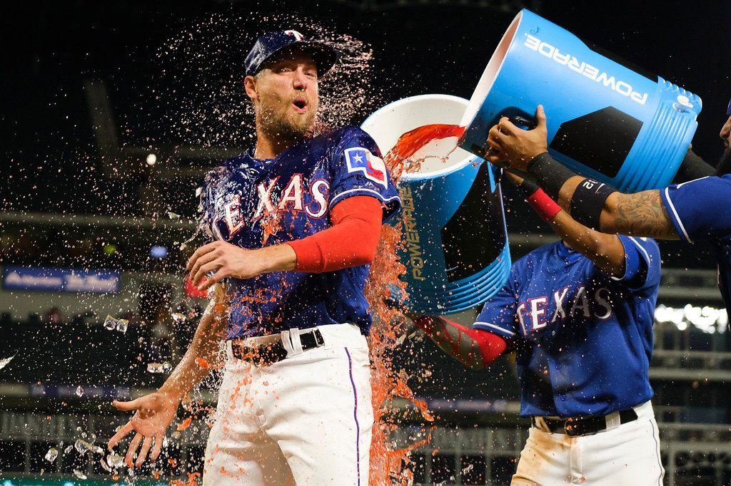 Texas Rangers outfielder Hunter Pence is doused with Powerade by shortstop Elvis Andrus and second baseman Rougned Odor after a victory over the Houston Astros at Globe Life Park on Wednesday, April 3, 2019, in Arlington. (Smiley N. Pool/The Dallas Morning News)