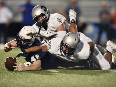 Guyer senior linebacker Dante Ramacher (25) and senior defensive end Cameron Wax (9) reach out for the ball after causing a fumble by Keller senior kicker Luke Hogan (45), Thursday, September 24, 2015, in Keller, TX. David Minton/DRC