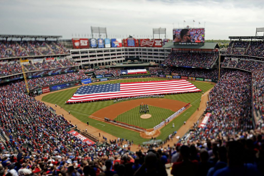 The American flag is unfurled on the field during the national anthem on Texas Rangers opening day Friday, April 10, 2015 at Globe Life Park in Arlington, Texas. (G.J. McCarthy/The Dallas Morning News)