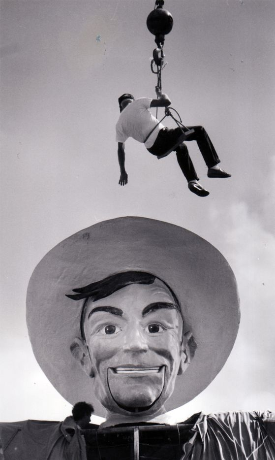 Oct. 25, 1988: Jack T. Bridges of Lancaster is lowered to the head of Big Tex so he and his partner, Richard Conger of Duncanville (seen removing bolts that fasten Big Tex's head to his frame), can affix it to a crane for removal.