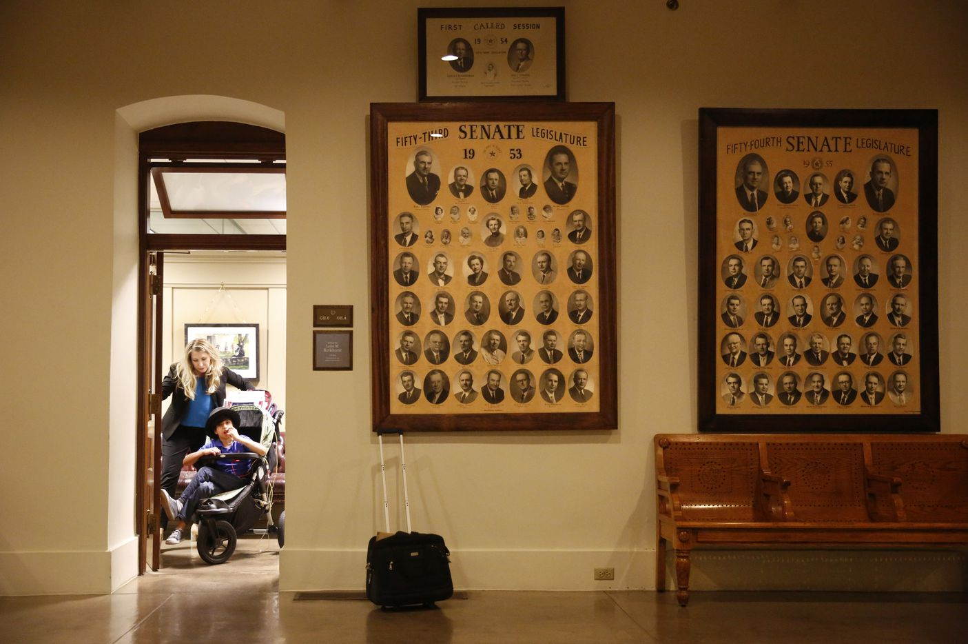 Hannah has trouble pushing Aiden through the door after visiting with staff in Senator Lois Kolkhorst's office at the Texas State Capitol. Photos of past Senators line the walls of the corridor.