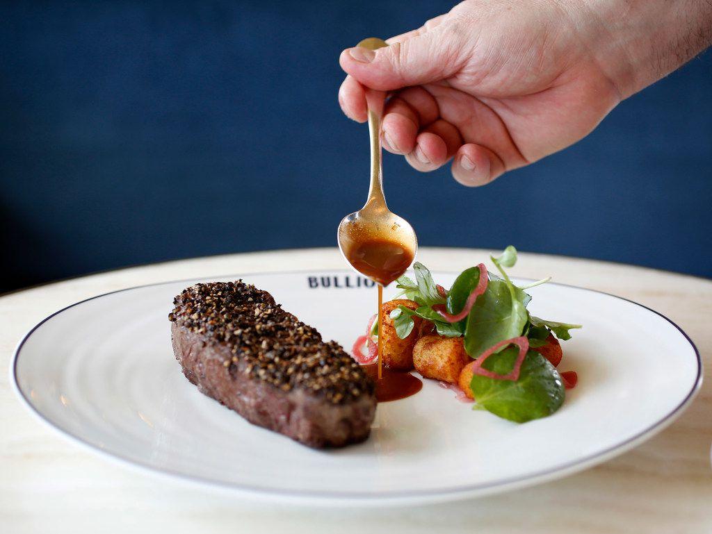 Chef Bruno Davaillon pours sauce on Bison Steak au Poivre.
