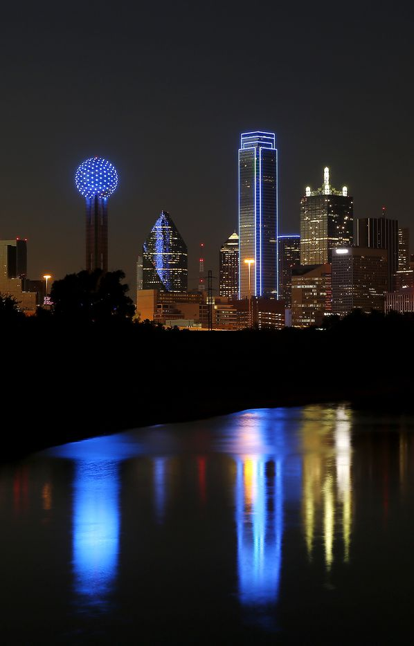 Reunion Tower (left) and Bank of America Plaza were lit in blue in honor of five police officers killed by the ambush attack in downtown Dallas, Tuesday, July 12, 2016.