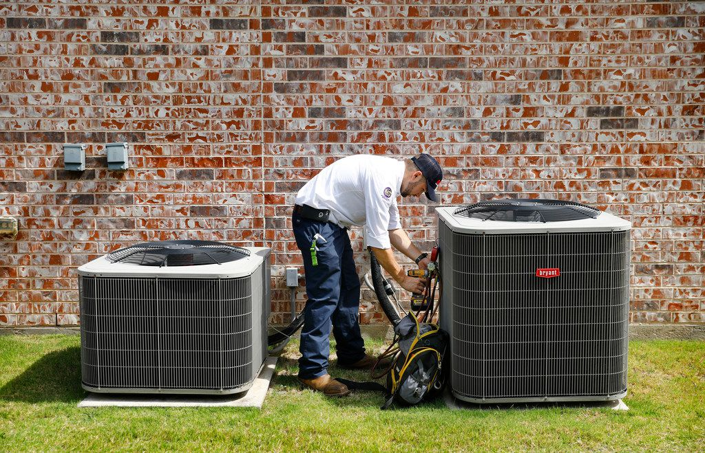 Berkey's Air Conditioning, Plumbing, and Electrical technician Brandon Cronkhite removes the panel to an outdoor condensing unit he inspected at a Southlake, Texas home, Friday, July 20 2018. (Tom Fox/The Dallas Morning News)