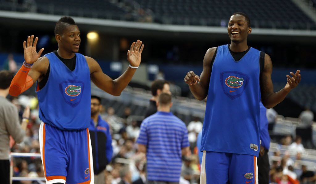 Florida Gators forward Will Yeguete (15) and Florida Gators forward Dorian Finney-Smith (10) share a laugh after they shot three pointers during an open practice at AT&T Stadium in Arlington, on Friday, April 4, 2014. (Vernon Bryant/The Dallas Morning News)  NCAA Final Four