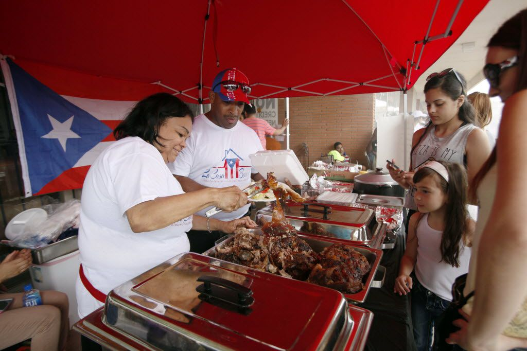 Bernice Castro (left) and her husband, Ismael Castro, served traditional Puerto Rican-style cooking to families during a Chinchorro party, hosted by the Puerto Rican Association of Dallas, in May 2016 in Fort Worth.