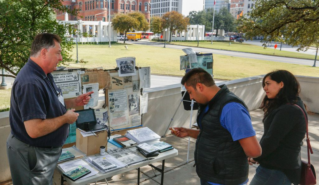 Mark A. Oakes, left, who calls himself a J.F.K. assassination researcher, answers questions form Sergio Garcia, center, and Marisol Hernandez at his display at Dealey Plaza Tuesday, November, 14, 2017. Oakes has been at Dealey Plaza selling various videos on the President Kennedy assassination since 1995. (Ron Baselice/The Dallas Morning News)