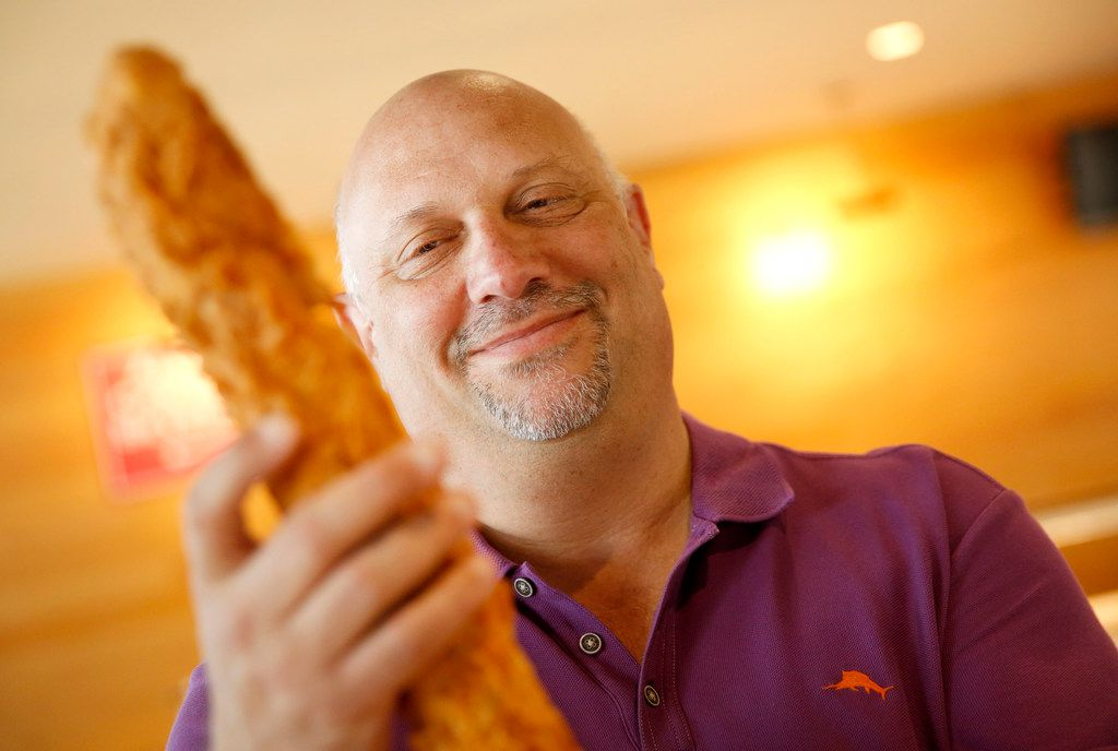 Dallas Morning News Texas Rangers writer Evan Grant tries the new Fowl Pole, a two-pound chicken tender at Globe Life Park in Arlington Texas on Monday, March 25, 2019. (Rose Baca/Staff Photographer)