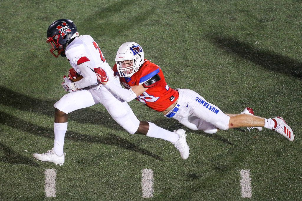 Justin Northwest's Zavion Taylor (2) carries the ball as he is brought down by Grapevine defensive back Dylan Hohenberger (38) during the first half of a high schools football game at Mustang-Panther Stadium in Grapevine, Texas on Thursday, September 12, 2019. (Shaban Athuman/Staff Photographer)