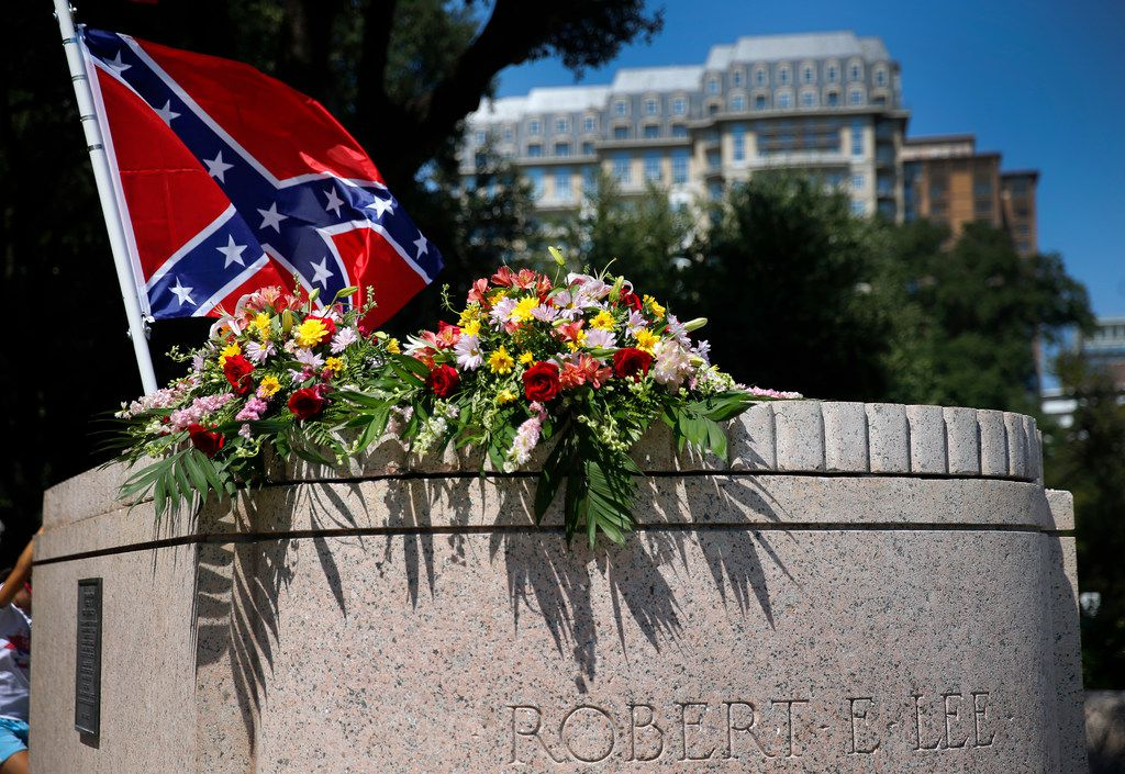 A Confederate flag flies over bouquets of flowers  placed on the Robert E. Lee statue base by members of the Texas Liberty Coalition at Lee Park in Dallas on Saturday.  People came to the This Is Texas Freedom Force rally to protest the removal of the Robert E. Lee statue.