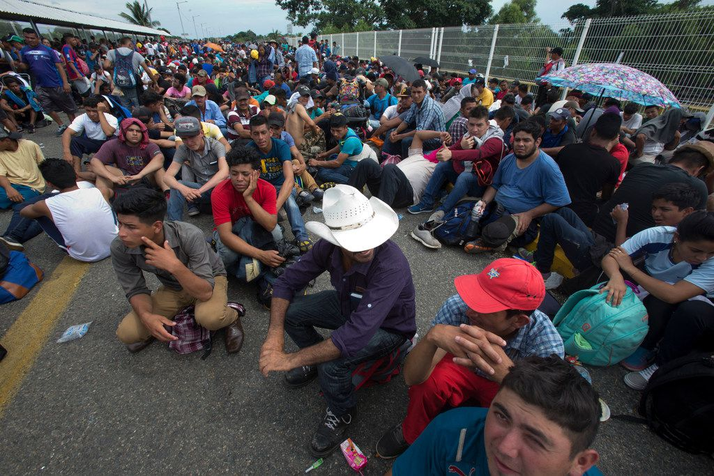 Central American migrants sits on the bridge over the Suchiate River that separates Guatemala and Mexico, in Tecun Uman, Guatemala on Friday.