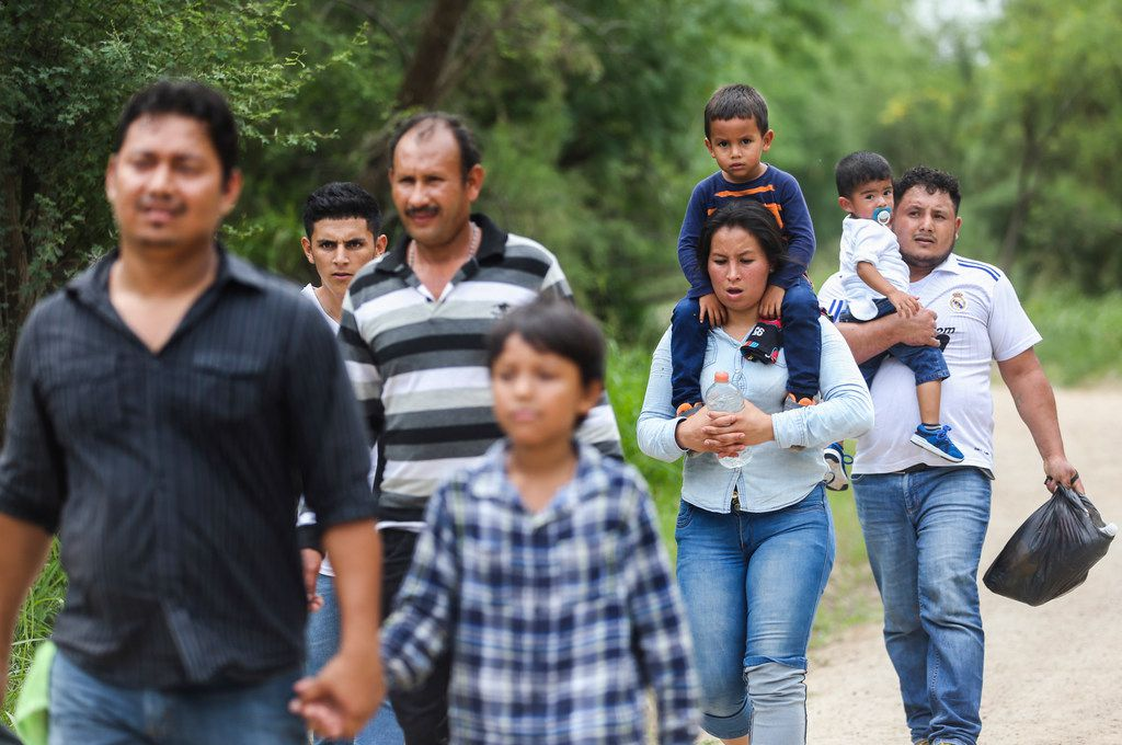 Central American asylum seekers walk up a road after crossing the Rio Grande on Friday, May 3, 2019, near McAllen.