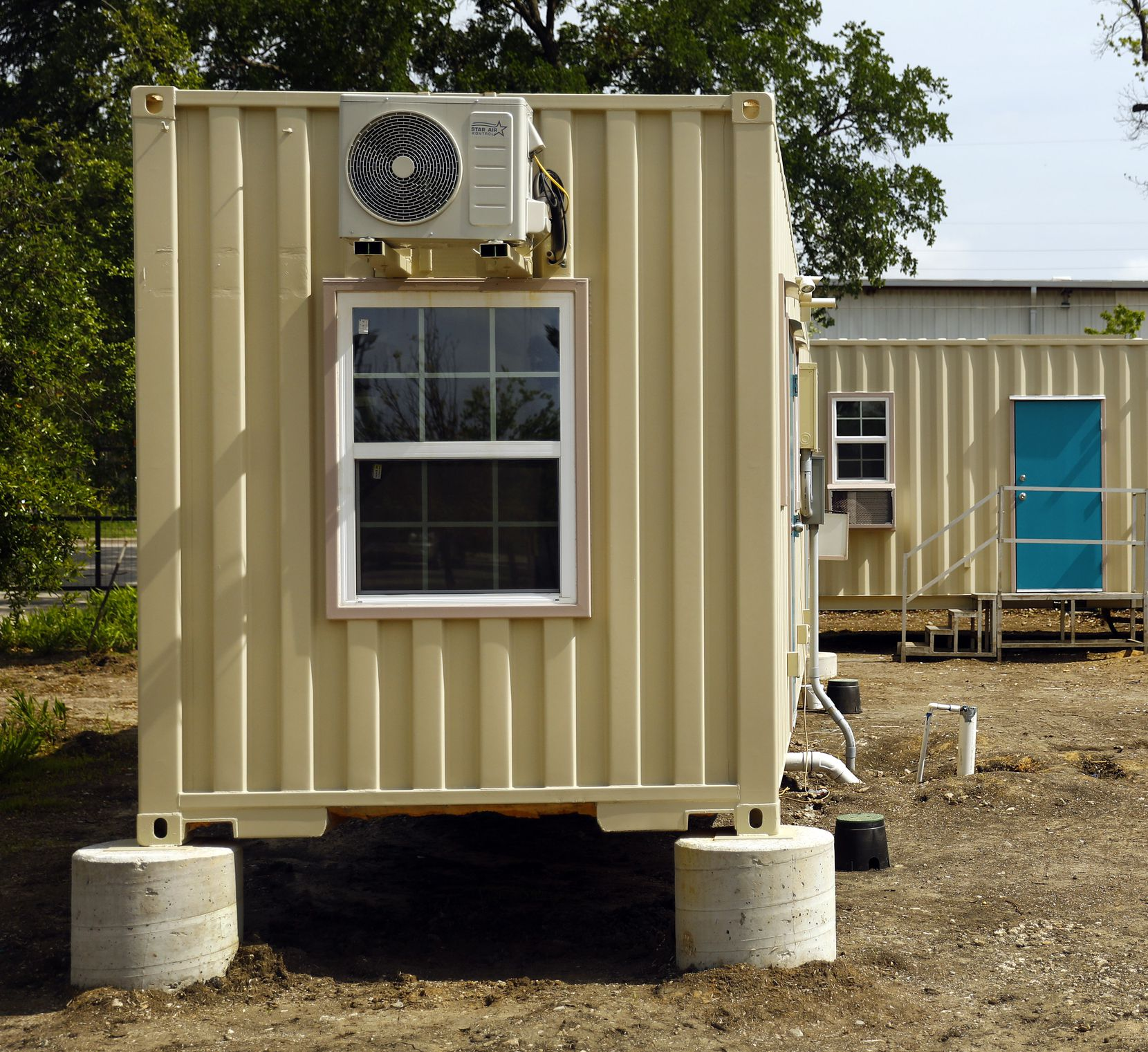 A pair of new experimental structures fabricated from recycled shipping containers are being finished out at The Cottages at Hickory Crossing. One of the 40-foot-long containers (left) houses two studio units, and the other has   a single, one-bedroom apartment.