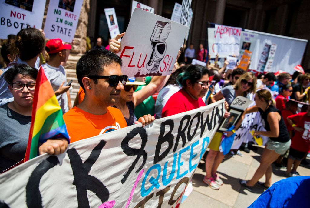 Alfonso Mendoza, left, of El Paso and other protesters held signs during a One Texas Resistance rally on the south steps of the Capitol on the first day of a legislative special session on Tuesday  in Austin.