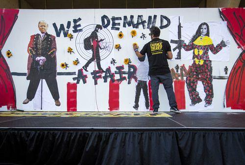 Manuel Oliver, padre de una de las víctimas de Parkland, pone flores en los agujeros que simbolizan las víctimas de Parkland, durante la protesa a favor del control de armas en el centro de Dallas. SMILEY POOL/DMN