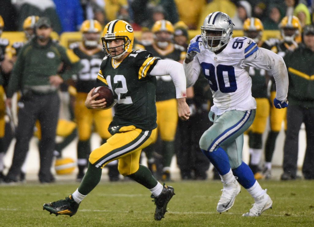 Dec 13, 2015; Green Bay, WI, USA;  Green Bay Packers quarterback Aaron Rodgers (12) runs past Dallas Cowboys defensive end DeMarcus Lawrence (90) for a first down in the fourth quarter at Lambeau Field. Mandatory Credit: Benny Sieu-USA TODAY Sports