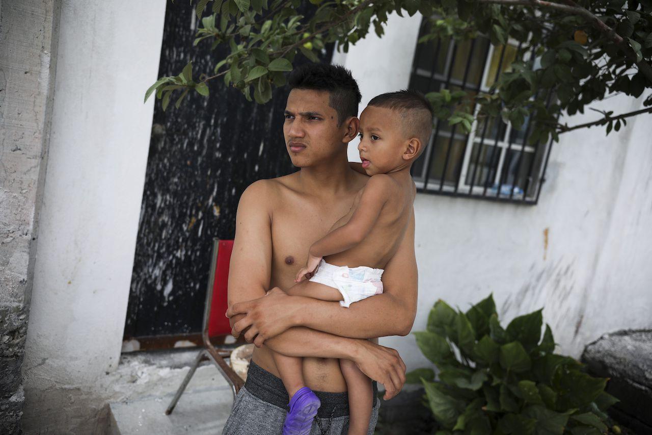 Gerardo, un migrante hondureño carga a su hijo Orlando, afuera de la iglesia Viento Recio en Matamoros, Mexico.