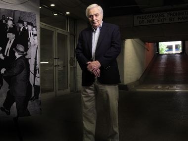 A 2013 photo of Hugh Aynesworth, former Dallas Morning New reporter and author of many books, near a photograph of Jack Ruby shooting and killing Lee Harvey Oswald (taken by Jack Beers of 'The Dallas Morning News') in the garage of the Dallas Police station. Hugh was about 40 feet away when he witnessed the event on November 24, 1963.