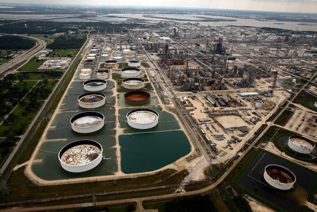 Large storage tanks situated in retention ponds are surrounded by rainwater left behind by Hurricane Harvey at ExxonMobil's refinery in Baytown, Texas, Wednesday, Aug. 30.