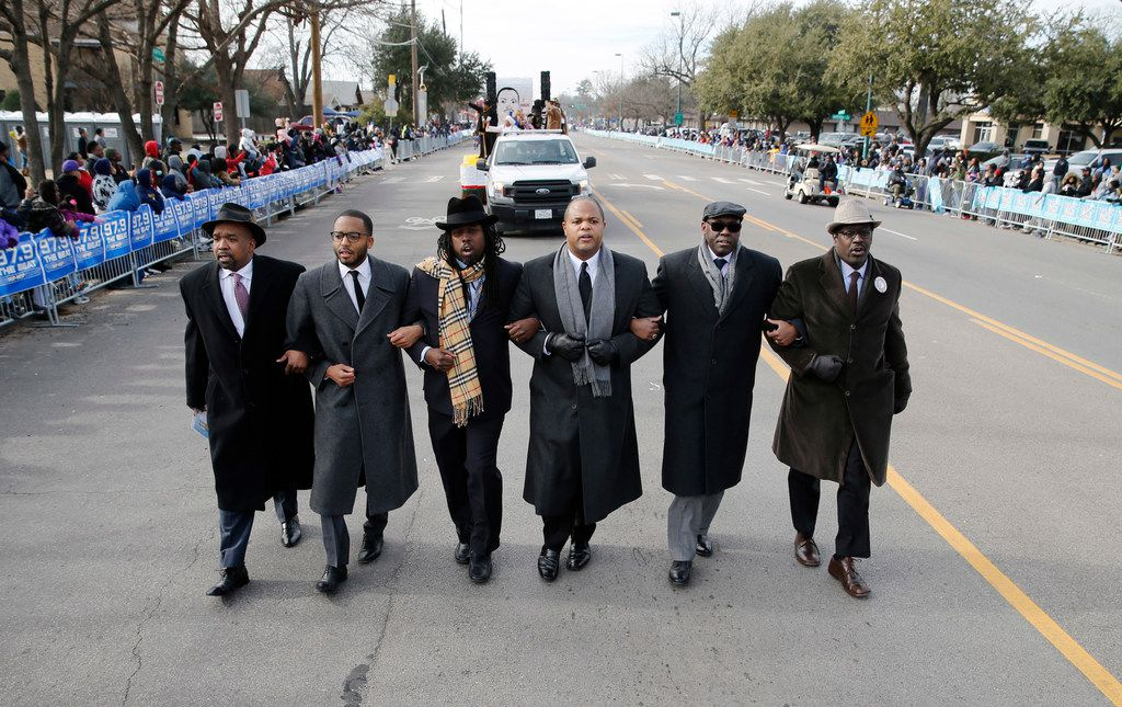Texas State representative Eric Johnson (second from right) walks arm in arm with people as they make their way down Martin Luther King Jr. Blvid. during the 37th Annual MLK Parade in Dallas on Saturday, January 21, 2019. (Vernon Bryant/The Dallas Morning News)