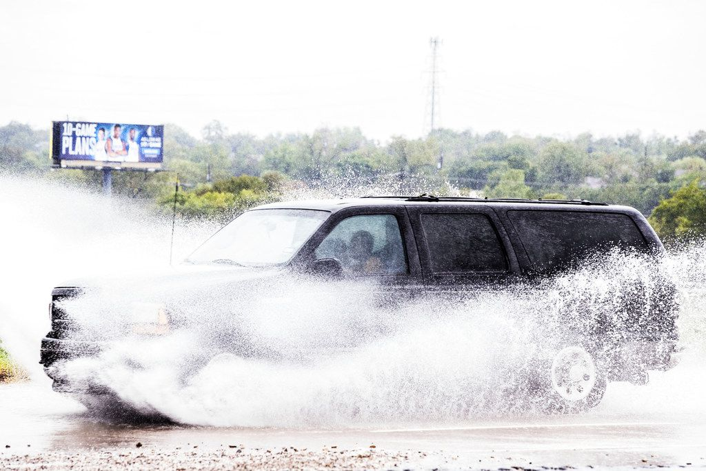 A truck drives through standing water at West Jefferson Boulevard and Loop 12 in Dallas on Oct. 13, 2018.  (Carly Geraci/The Dallas Morning News)