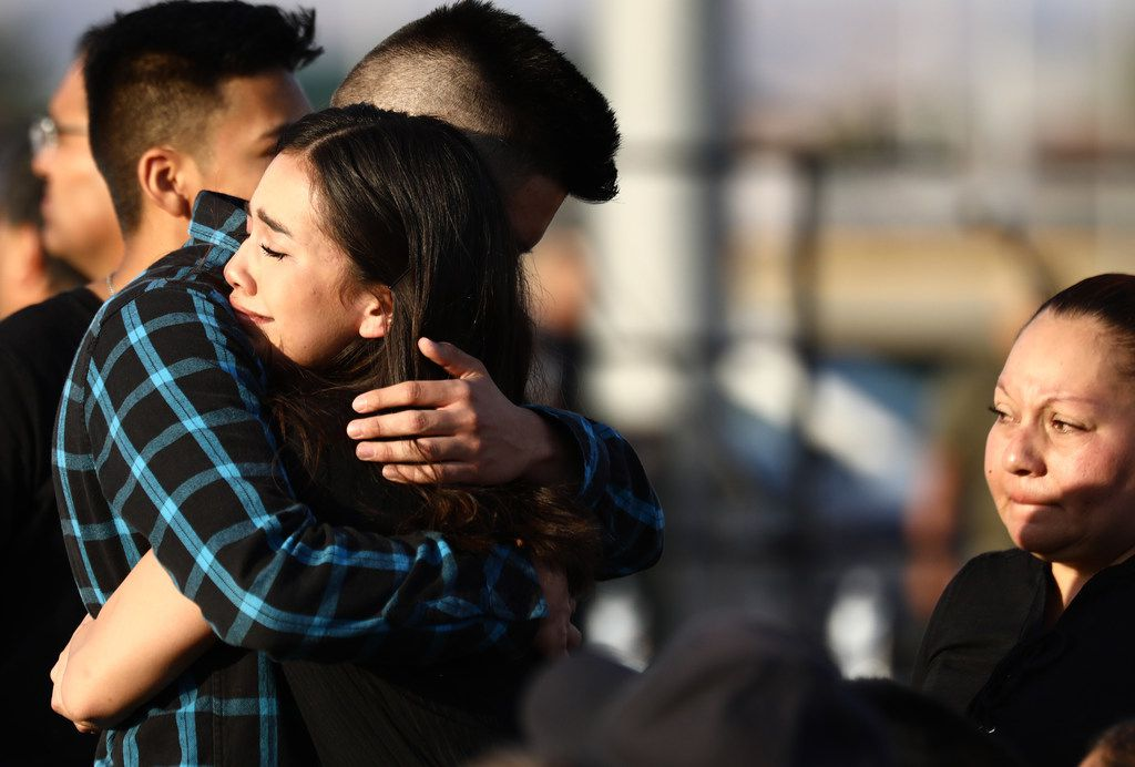 Mourners embrace at a vigil honoring Horizon High School sophomore Javier Amir Rodriguez, who lost his life in a mass shooting in nearby El Paso. The vigil was held at the school's football field. At least 22 people were killed in the shooting Saturday.
