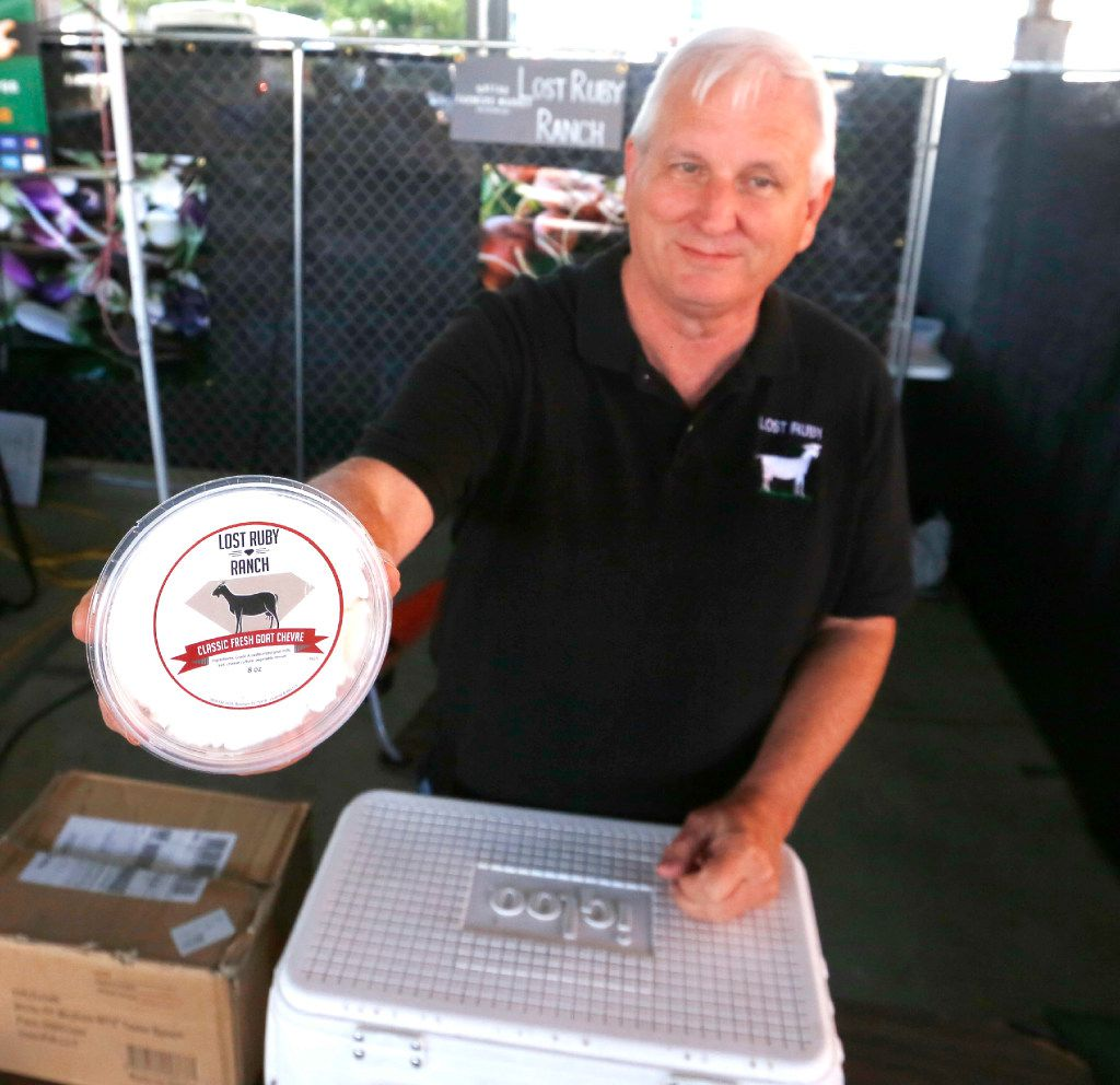 Paul Allen of Lost Ruby Ranch offers goat cheese at his booth at the Dallas Farmers Market.