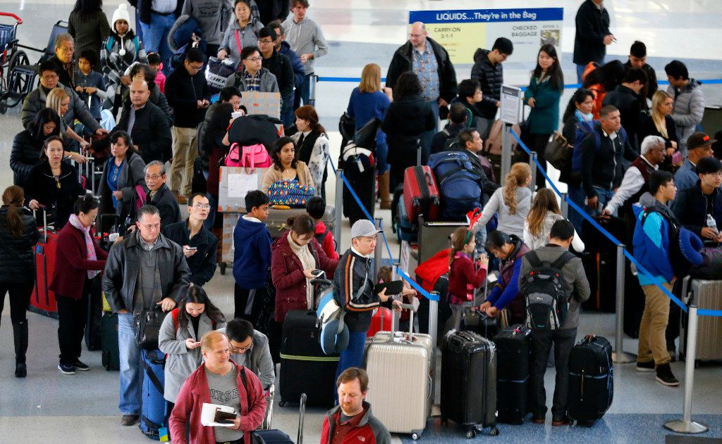 American Airlines passengers wait in a long line to get checked in at Terminal D at Dallas-Fort Worth International Airport, Thursday, December 8, 2016. (Tom Fox/The Dallas Morning News)