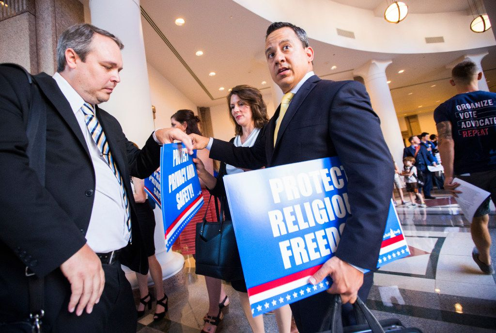 Jonathan Saenz, center, president of Texas Values, hands out signs as people stand in line to voice their opinions on the bathroom bill at a public hearing on the fourth day of a special legislative session on Friday, July 21, 2017 at the Texas state capitol in Austin, Texas. (Ashley Landis/The Dallas Morning News)