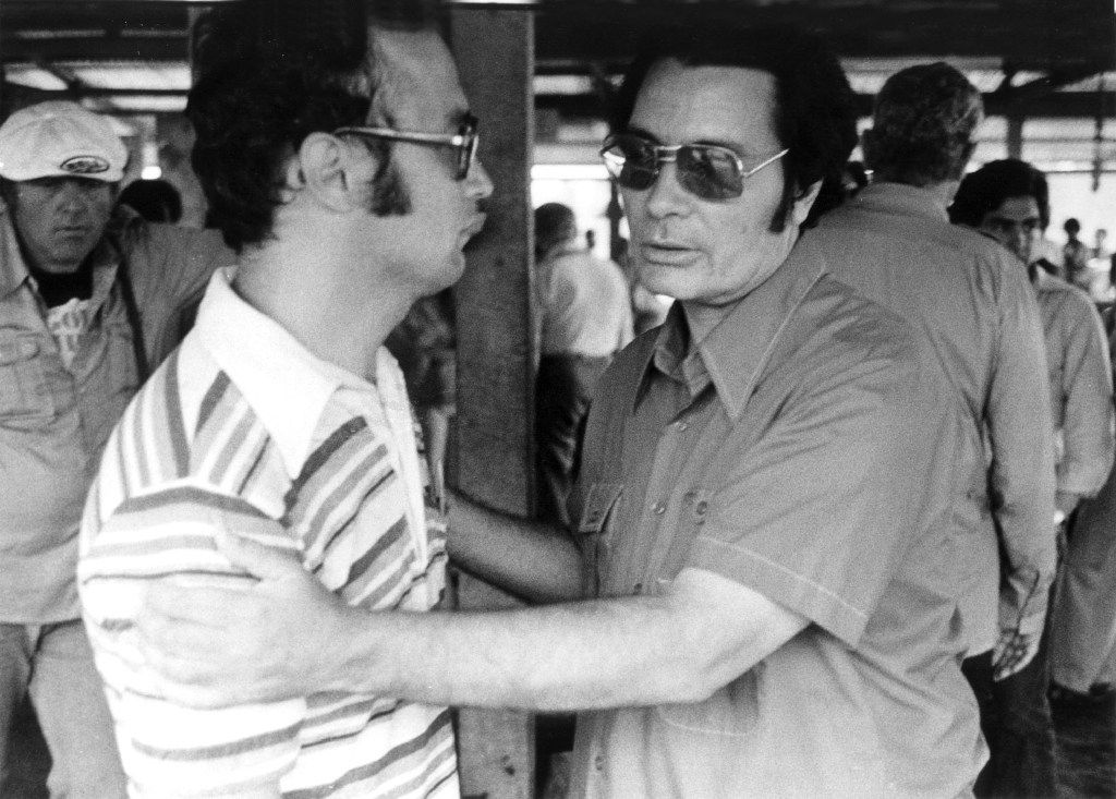 The Rev. Jim Jones, founder of Peoples Temple, clasps an unidentified man at Jonestown on Nov. 18, 1978,  during Congressman Leo J. Ryan's visit. Shortly after, Ryan, newsman Don Harris, cameraman Bob Brown and San Francisco Examiner photographer Greg Robinson, who took this photo, were killed in ambush at Port Kaituma, Guyana. (Greg Robinson)