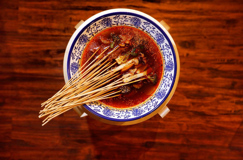 Skewers in large simmering bowl of medium, spicy chicken broth with Sichuan peppers is served at Chuan Chuan Boiled Skewer in Plano