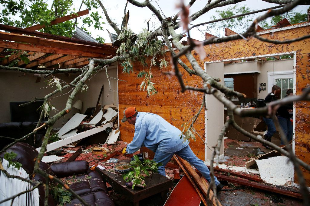 Andy Teague begins clearing debris from his living room along County Road 1910 after a tornado hit Fruitvale on Saturday. Teague took shelter in a tiled-shower with his wife, daughter and two dogs as tornadoes sweapt the area.