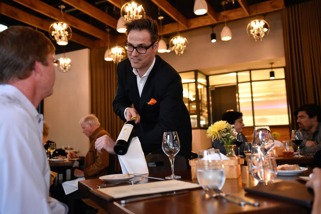 It's half price on Tuesday: Roger Bissell serves a bottle from the cellar at Mille Lire in Uptown.