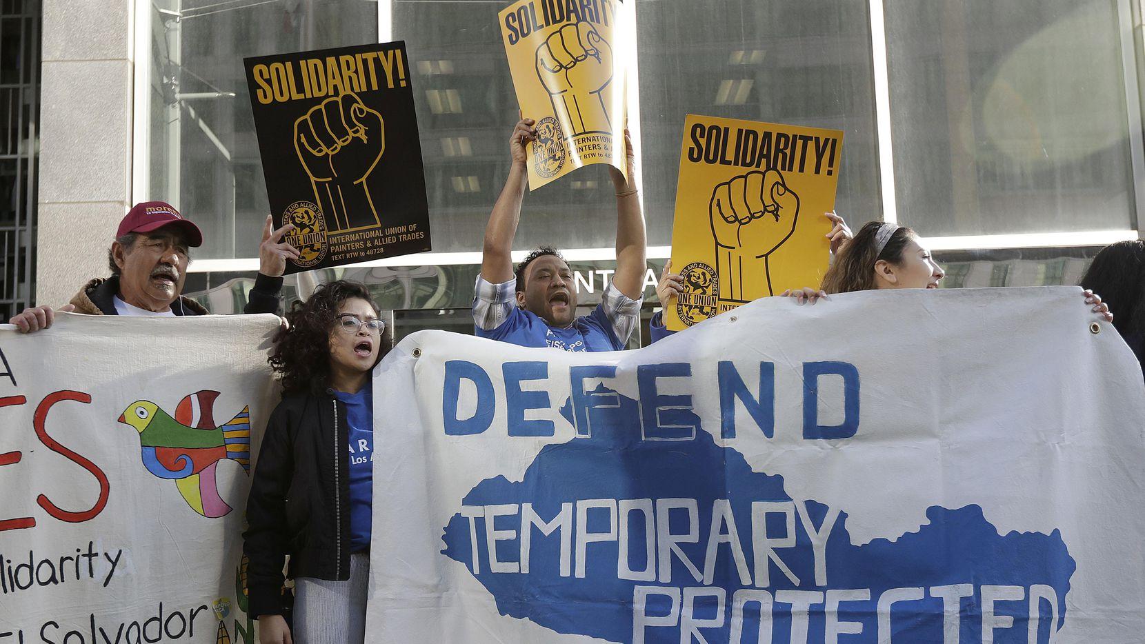 Personas portan pancartas de apoyo a programas de protección temporal en un evento afuera de la corte federal de San Francisco.(AP)