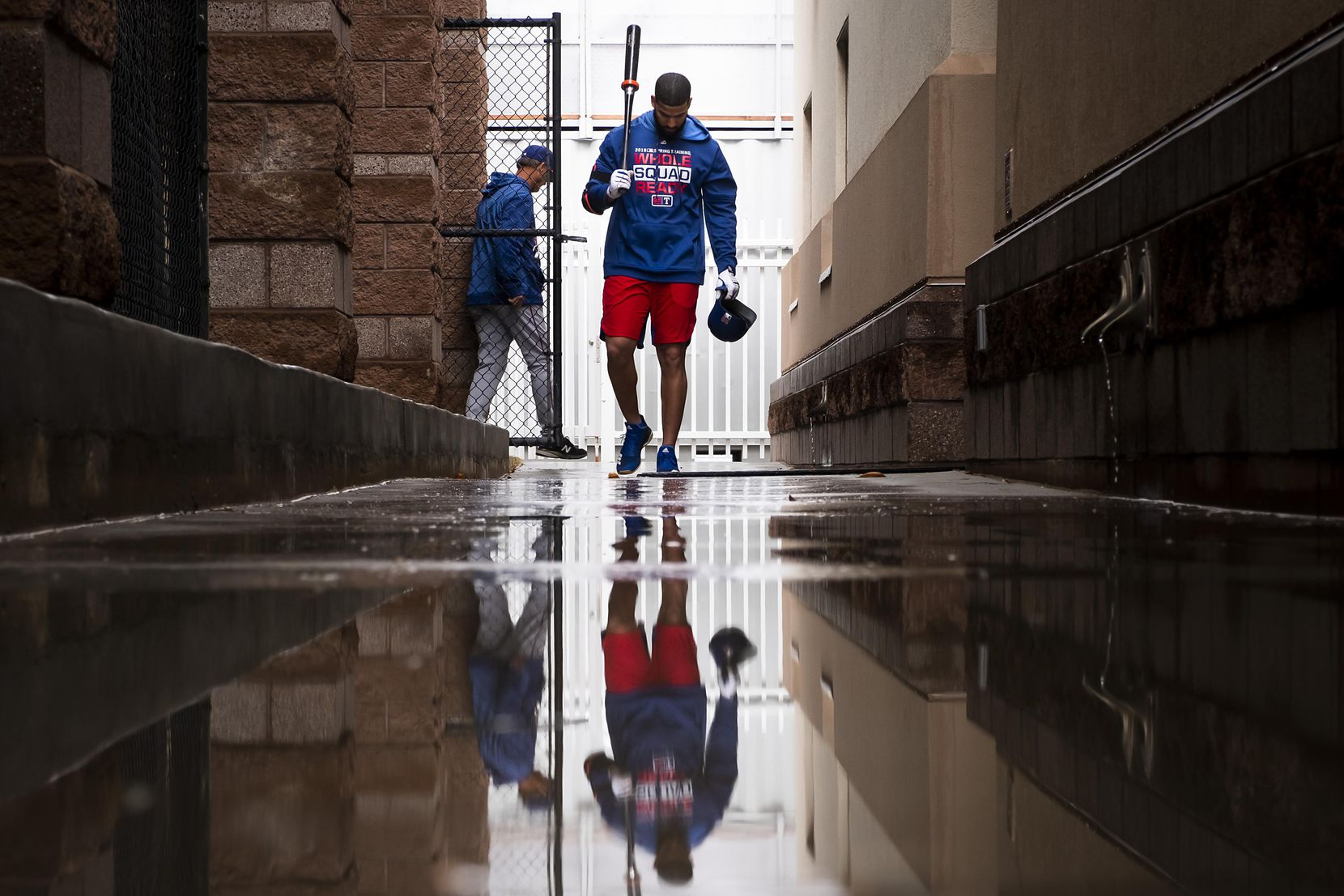 Texas Rangers outfielder Nomar Mazara walks through puddles as he heads from the batting cages to the clubhouse on Feb. 21 at the team's spring training facility in Surprise, Ariz.