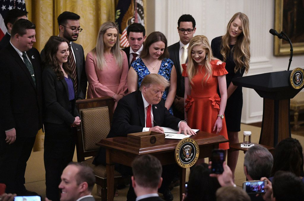 """U.S. President Donald Trump signs an executive order to require colleges and universities to """"support free speech"""" on campus or risk loss of federal research funds during an event in the East Room of the White House on Thursday, March 21, 2019."""
