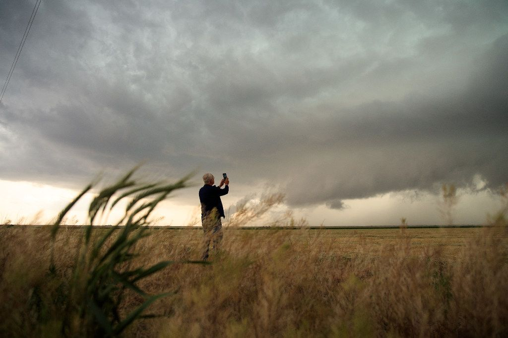 Support scientist Tim Marshall, a 40-year veteran of storm chasing, photographs a supercell thunderstorm during a tornado research mission on May 9, 2017, in Lamb County.
