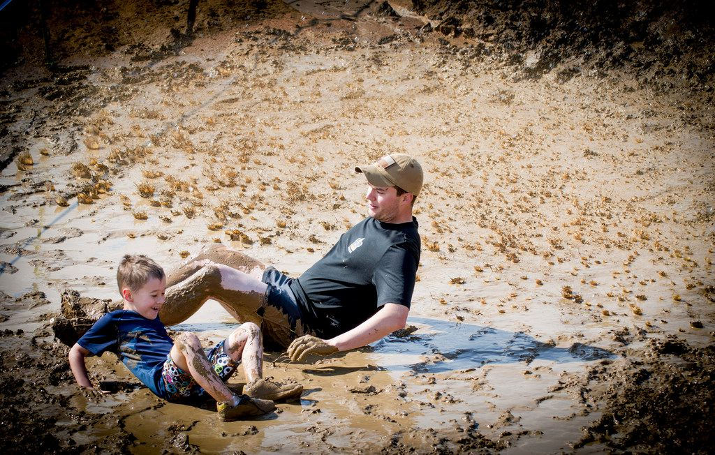 A father and son team frolic in the mud during the Kids Obstacle Challenge.