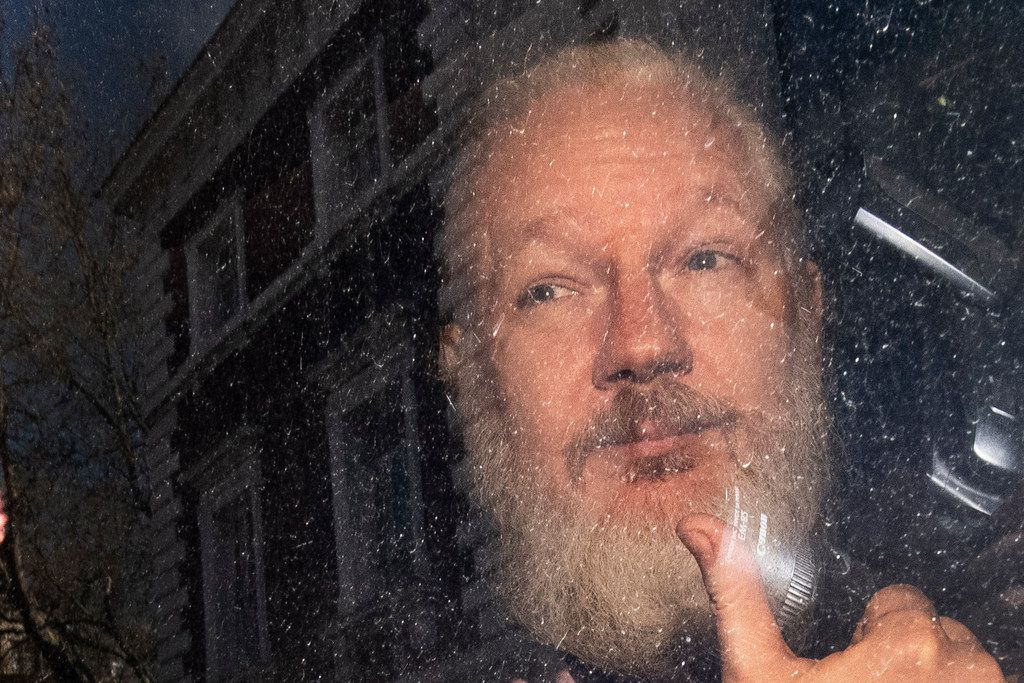 Julian Assange gestures as he arrives at Westminster Magistrates' Court in London, after the WikiLeaks founder was arrested by officers from the Metropolitan Police and taken into custody April 11, 2019.