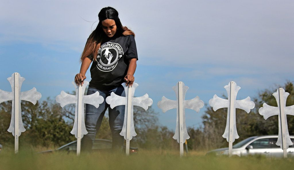 Sheree Rumph of San Antonio prays over 26 crosses placed near U.S. Highway 87 just down the block from Sutherland Springs Baptist Church.