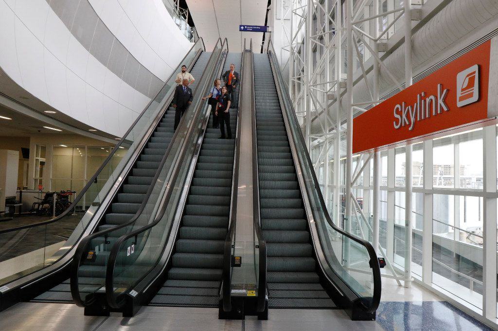 Travelers ride down an escalator in the newly remolded Terminal E at s Fort Worth International Airport on Wednesday, August 23, 2017. Today marks the second completed terminal in DFW's $2.7 billion Terminal Renewal and Improvement Program to renovate three of it's original terminal buildings. (David Woo/The Dallas Morning News)