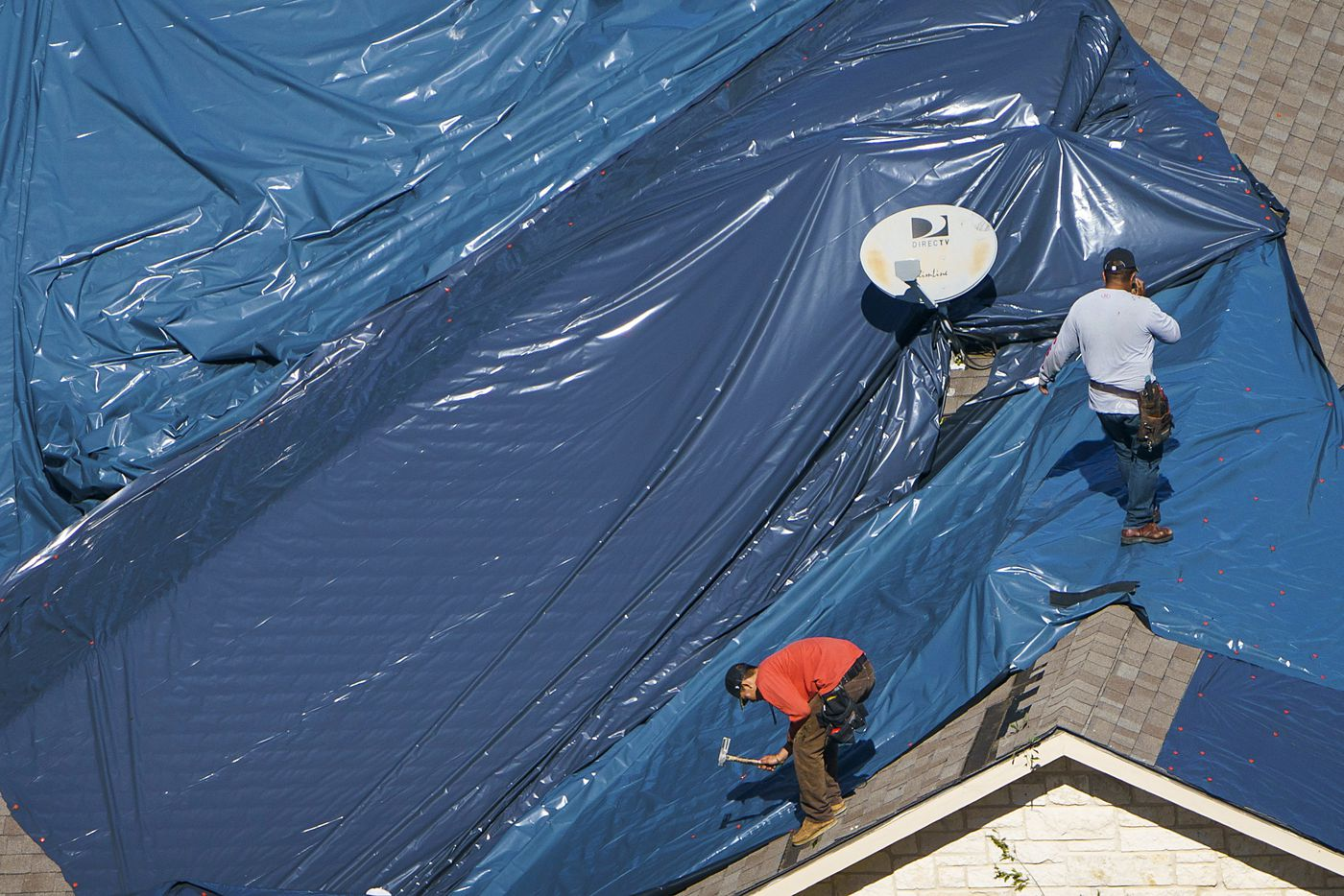Workers install a tarp over a tornado damaged roof of a home near Walnut HIll Lane and Mash Lane on Monday, Oct. 21, 2019, in Dallas.