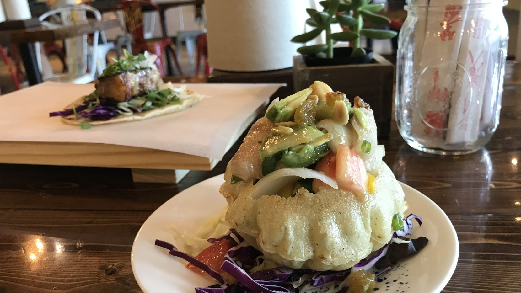 Chef Paul Qui, who has been at the center of a public domestic abuse case, recently opened a Japanese taco shop in Richardson called TacQui. Pictured: the crudo tostada with yellowtail and the pork belly taco.