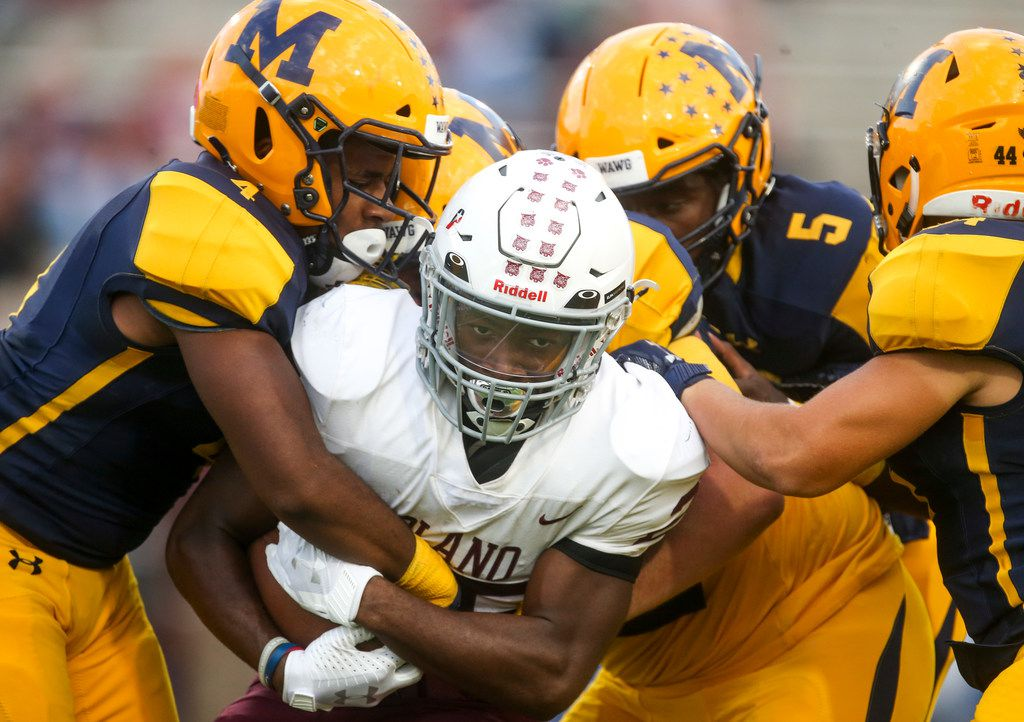 Plano running back Tylan Hines (center) gets tackled by a herd of McKinney defenders during the first half of a high school football game between McKinney and Plano high schools on Thursday, October 10, 2019 at McKinney ISD Stadium in McKinney, Texas. (Shaban Athuman/Staff Photographer)