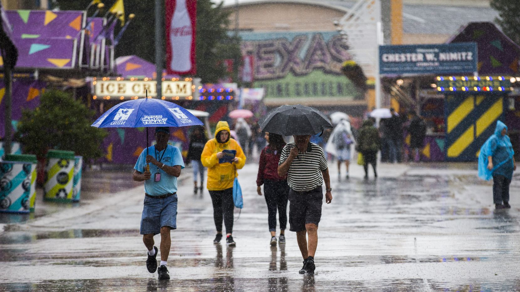 Fairgoers walk through the rain on the Midway at the State Fair of Texas.