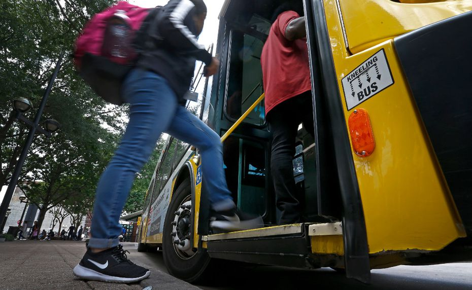 People board a DART bus at West Transfer Center in Dallas.