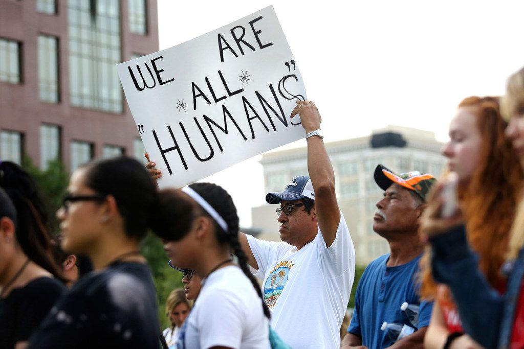 """Pablo Rodriguez holds up a sign reading """"We Are All Humans"""" during a vigil to remember the victims of the El Paso and Dayton, Ohio, mass shootings and call for lawmakers to take action against gun violence, Aug. 11, 2019, at Miller Park in Chattanooga, Tenn."""